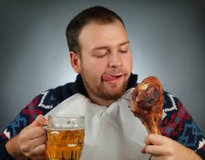 man eating turkey drinking beer